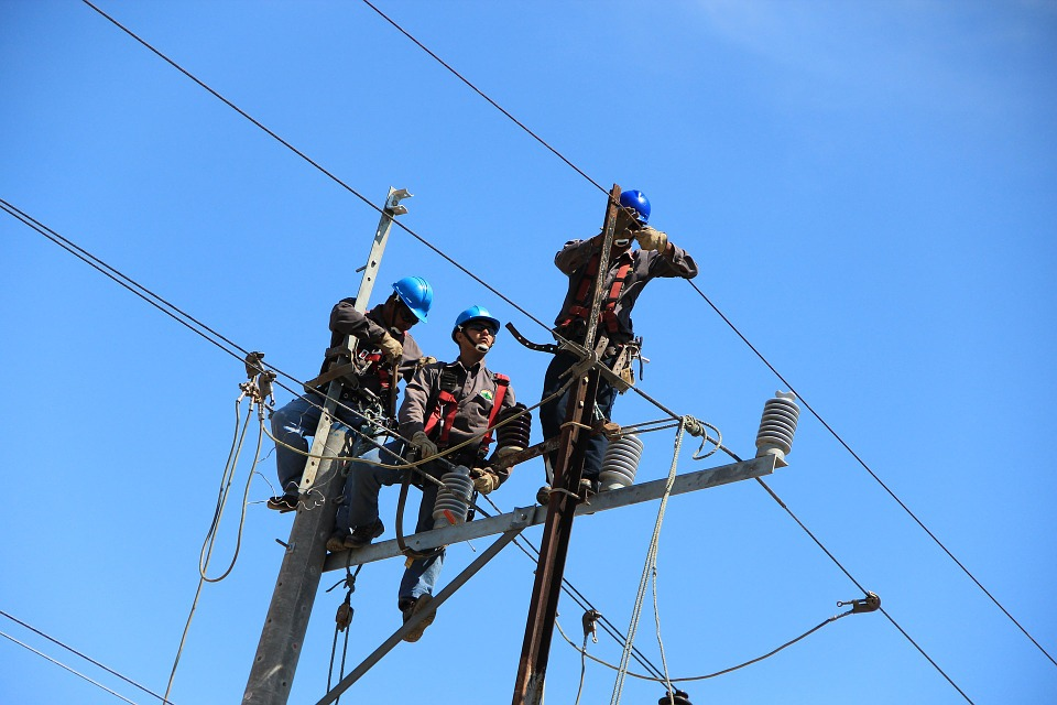 Electricians working on phone and electrical wires atop utility pole.