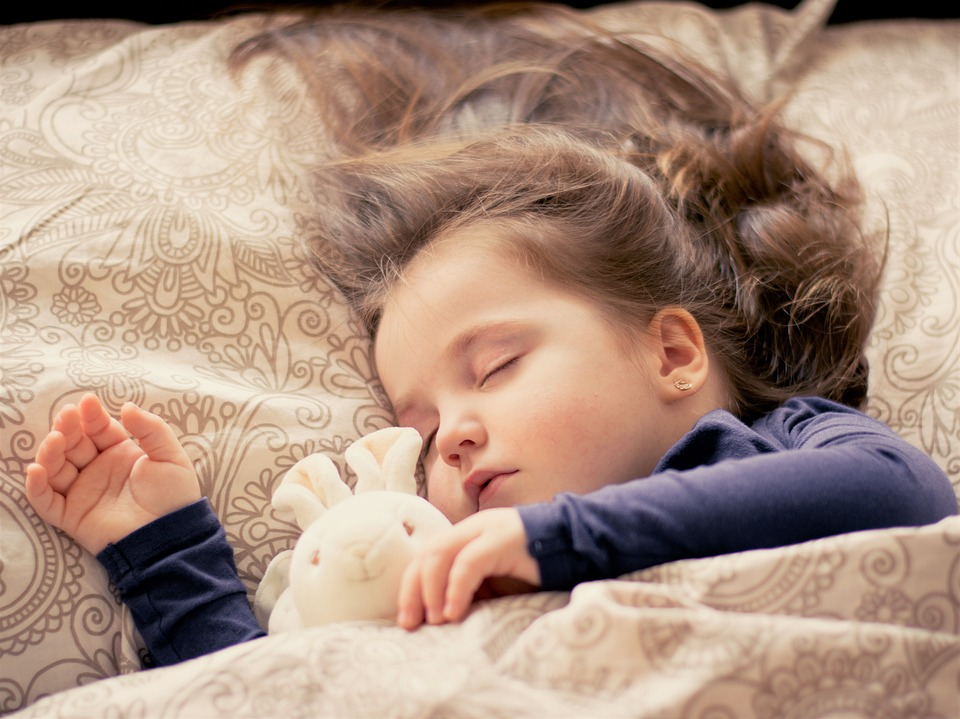 A child sleeping with a stuffed rabbit.