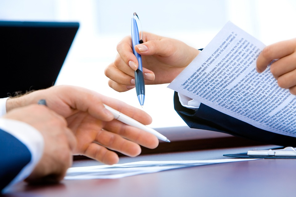 Two business people signing contracts.
