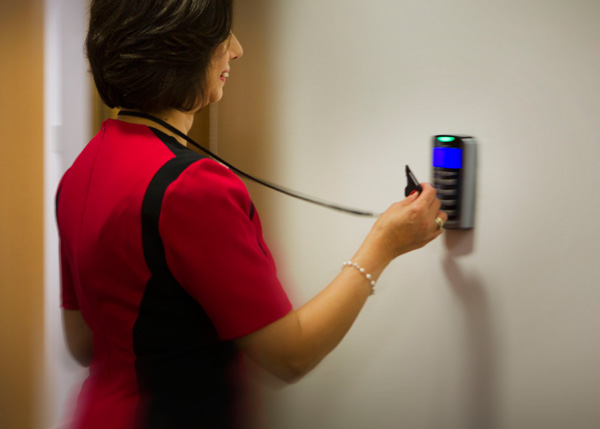 An employee using an AMAG access card to unlock a door