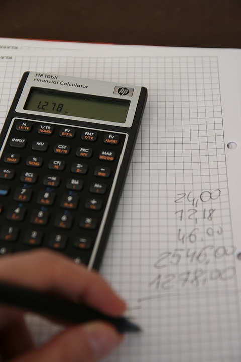 Someone using a calculator, paper, and pen to add numbers.