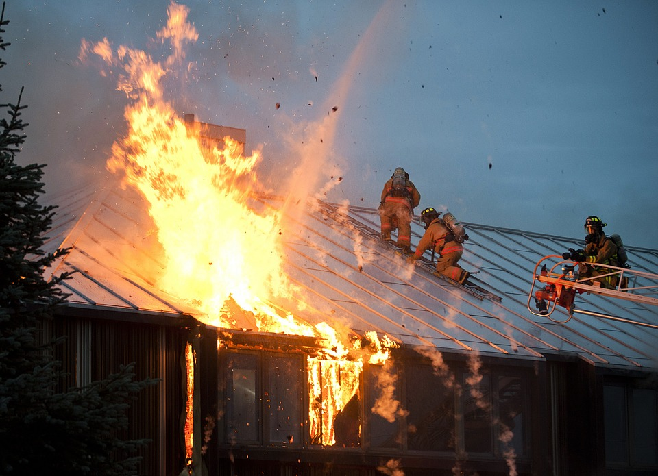 Firefighters fighting a fire at a burning home.