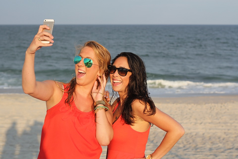 2 girls taking a picture of themselves on the beach.