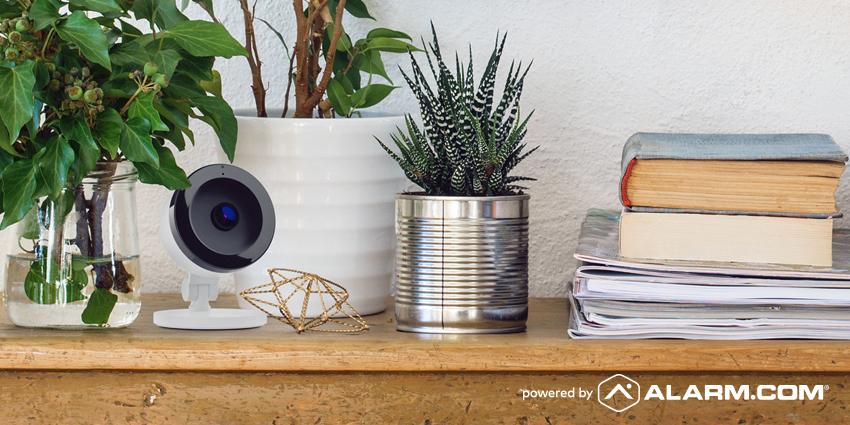 An Alarm.com camera on a shelf with household items.
