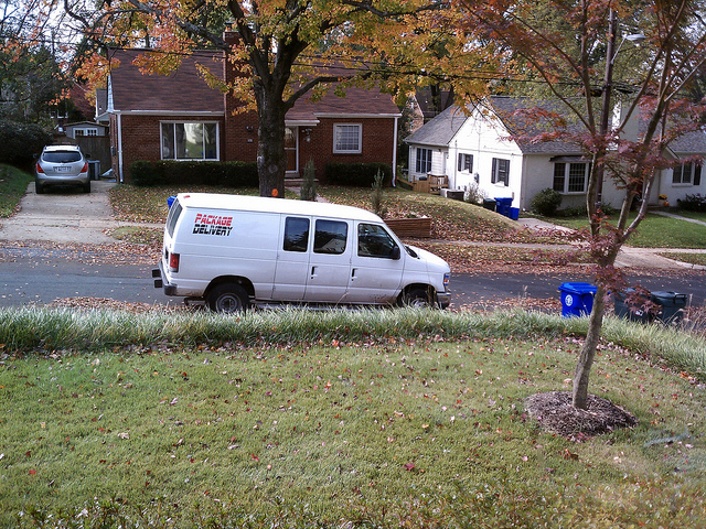 A white van parked outside a house.