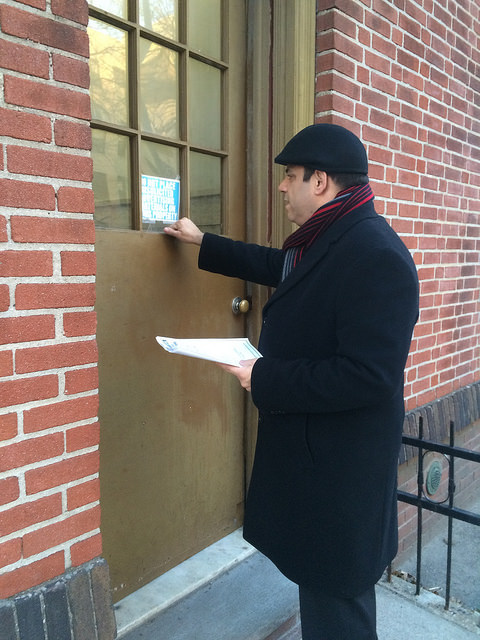 A man with a paper knocking on a door.