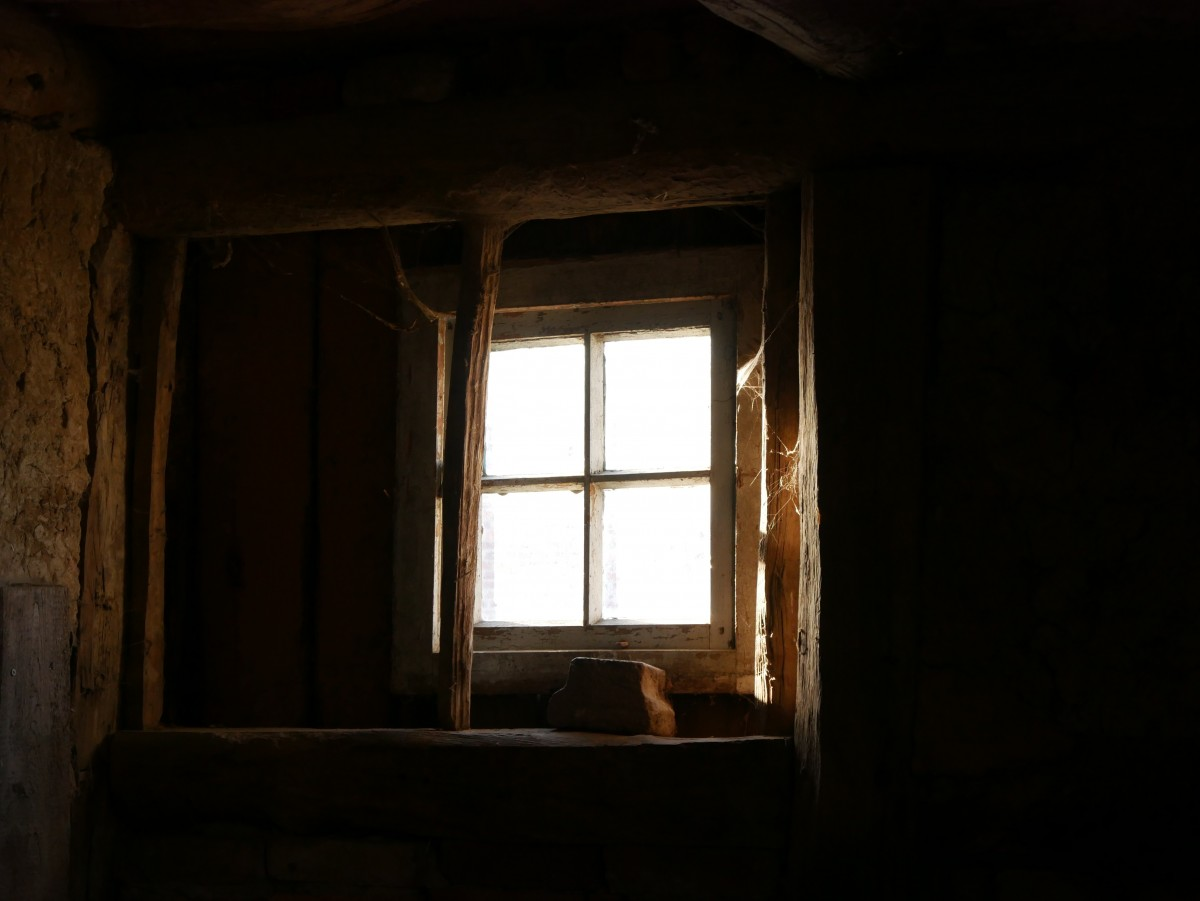 A basement window with light streaming through