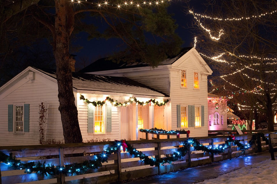A house and fecne decorated with Christmas lights.