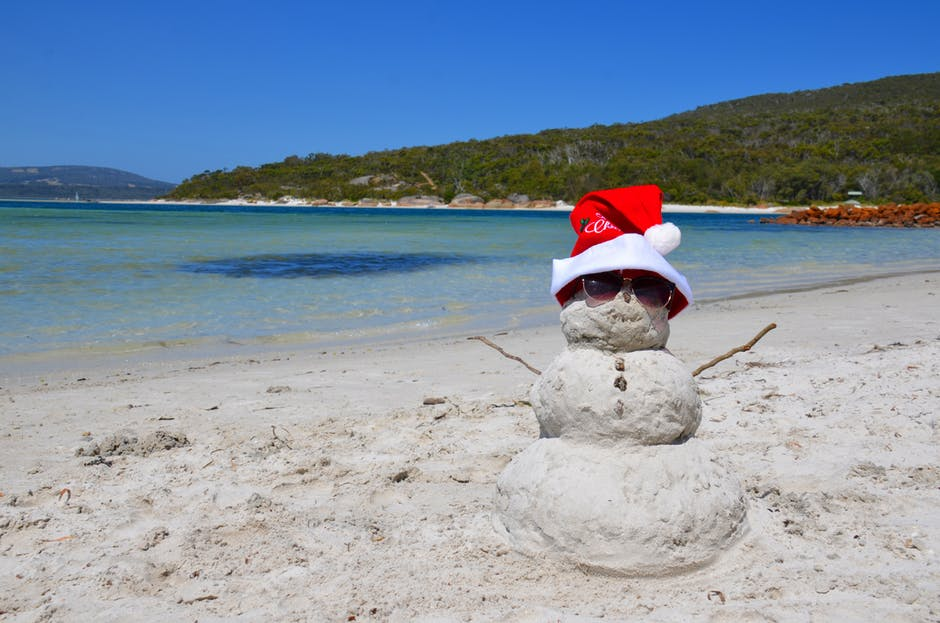"""A """"snowman"""" made out of sand on a beach with a santa hat."""