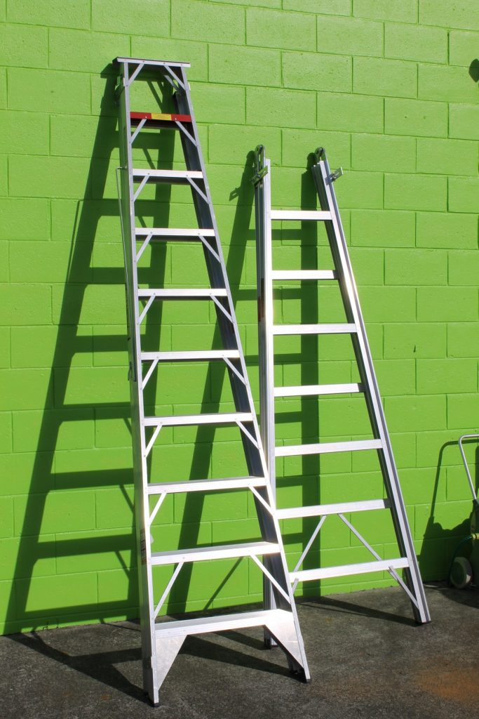 Two ladders leaning against a green cement wall.