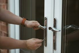 A pair of hands opening a door with a key.