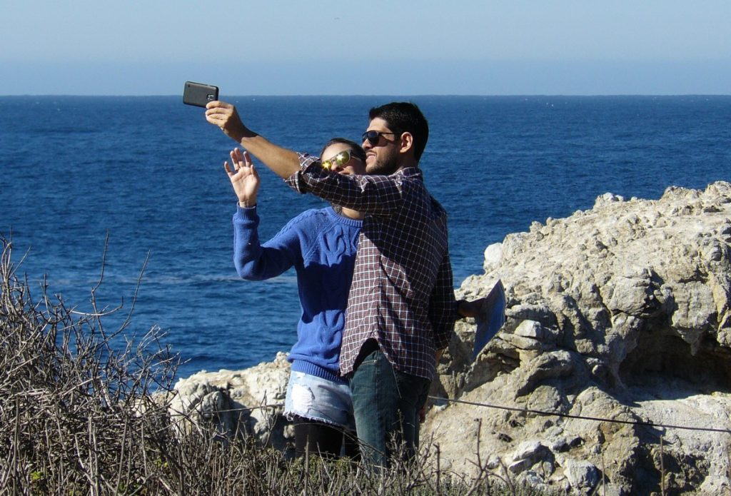 Two people taking a selfie on a beach.