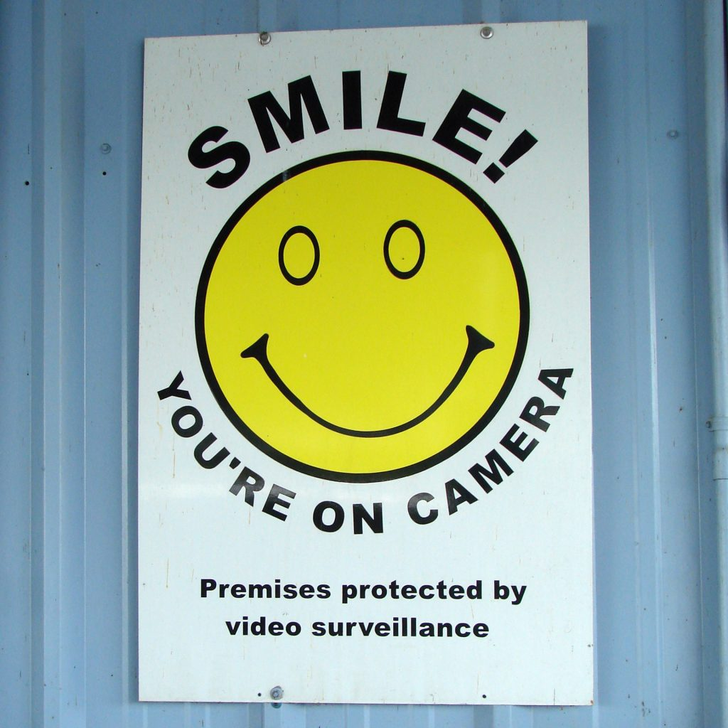 "A sign reading ""SMILE! YOU'RE ON CAMERA"""