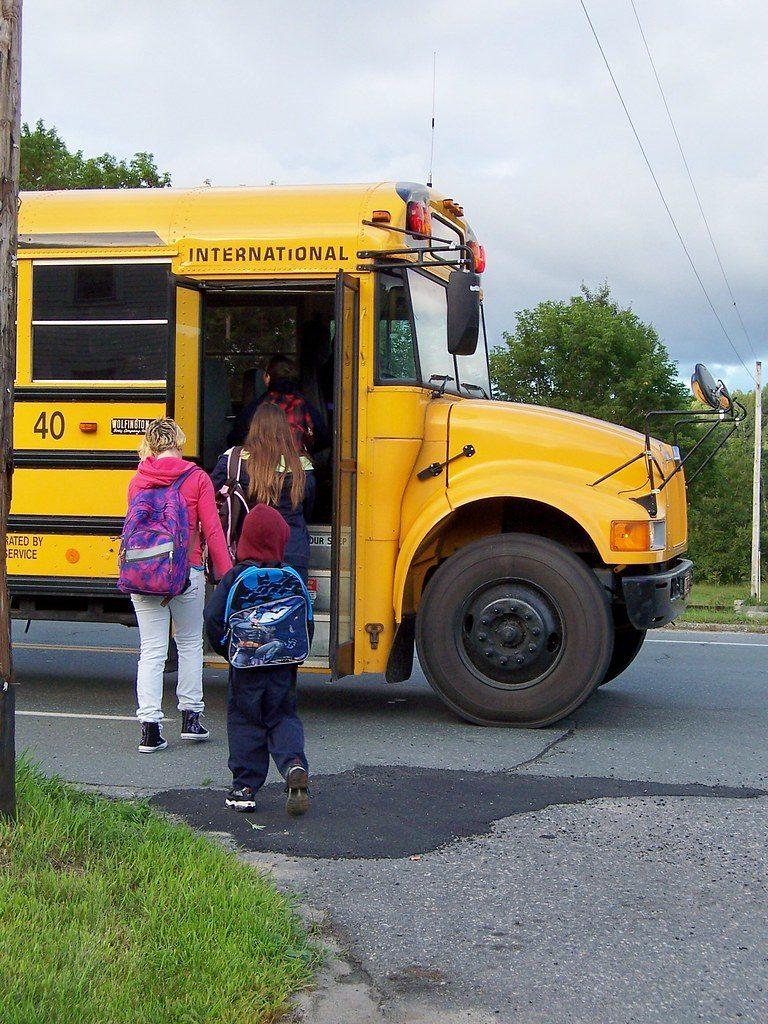 Children climbing on to school bus.