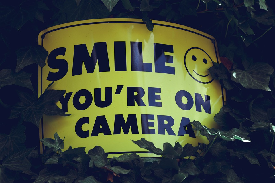 "A sign reading ""Smile, You're on Camera"""