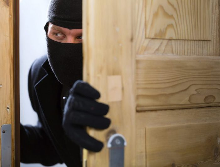 Burglary crime - burglar opening a door