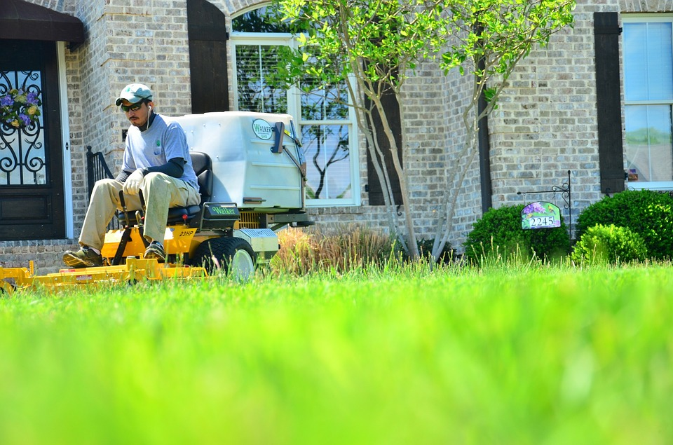 A lawn care worker on a riding mower.