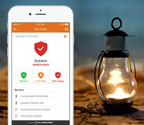 An Alarm.com app open n a smartphone indicating an armed security system, next to a lantern