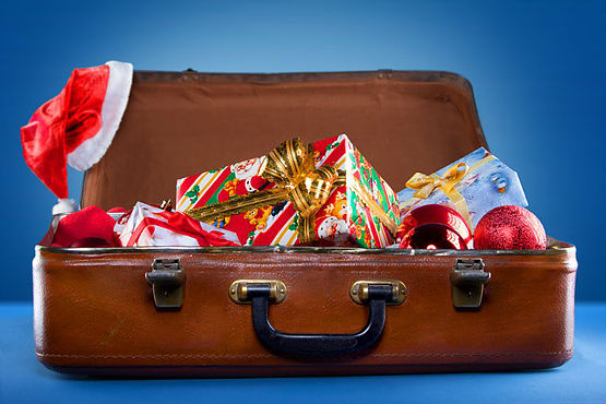 A suitcase filled with gift-wrapped packages and holiday decorations