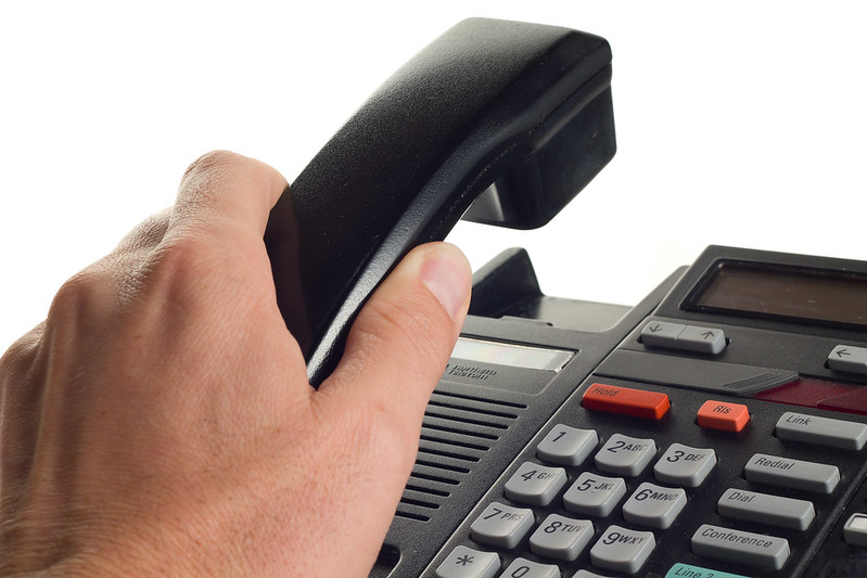 A hand picking up a phone