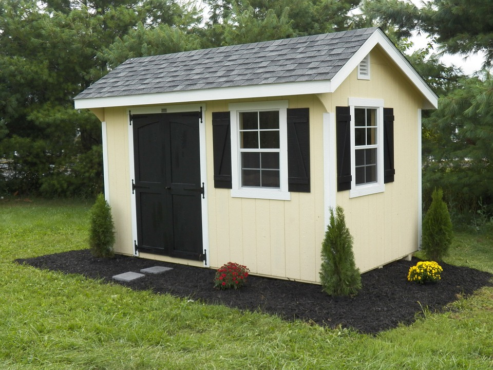 A yellow shed in a yard