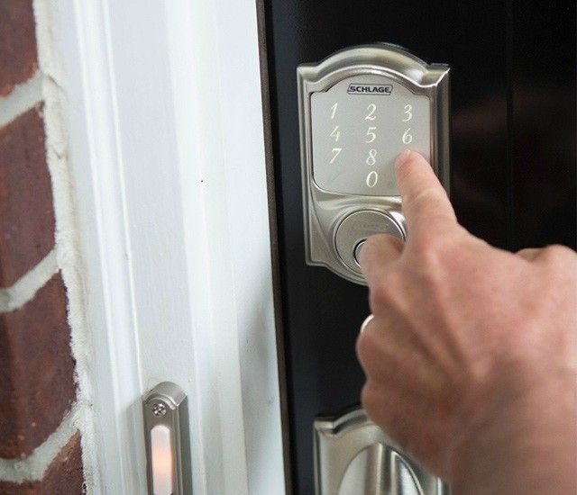 A Schlage smart lock on a door with a hand punching in a user code