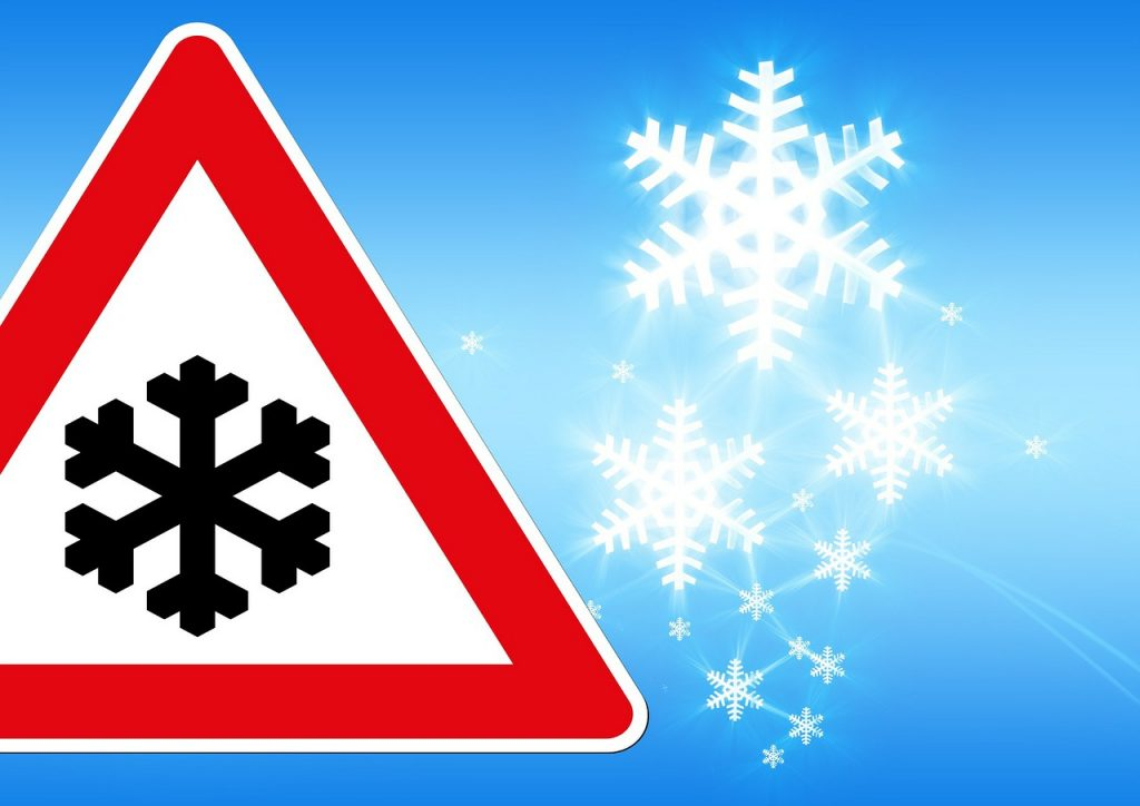 A traffic sign with a snowflake on it, with snow falling in the background
