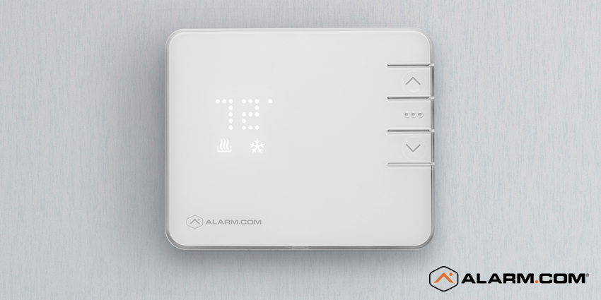 An Alarm.com smart thermostat on a wall