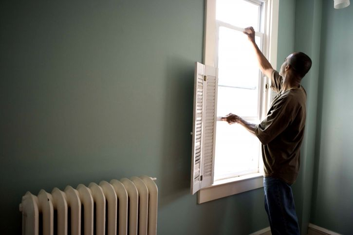 A man opening a window in a home